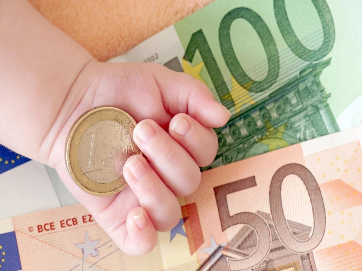 Hand von einem Baby mit Geld
